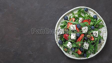 salad with arugula feta strawberry blueberry
