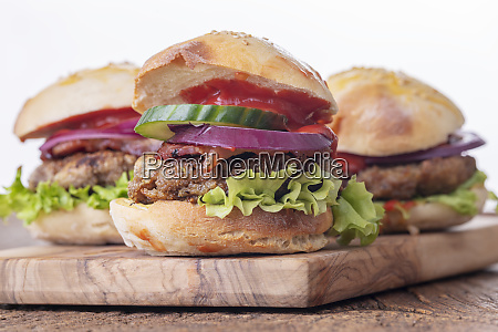 four hamburgers on dark wooden