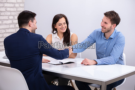 advisor handshaking with couple after deal