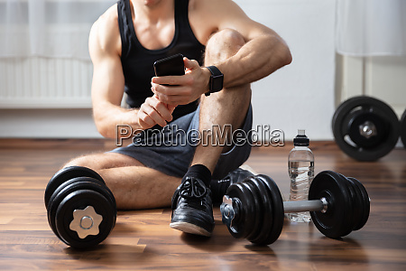 man using cellphone in gym