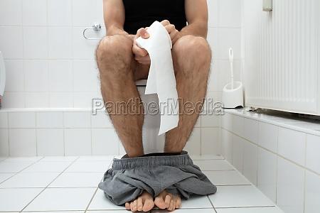 man sitting on toilet bowl holding