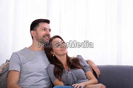 contemplated couple sitting on couch at