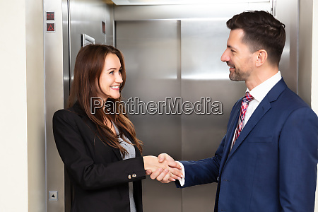 businesspeople shaking hands near elevator