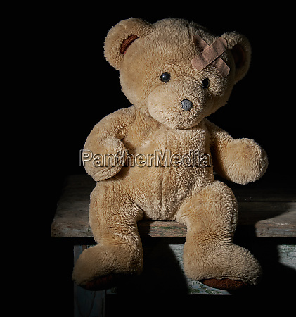 aold brown teddy bear is sitting