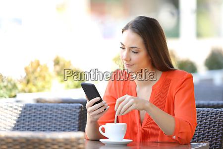 woman stirring coffee checking smart phone