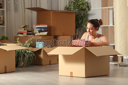 serious woman moving home unboxing belongings