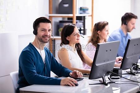 smiling customer service executives using earphones