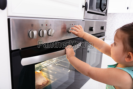 girl adjusting temperature of microwave oven