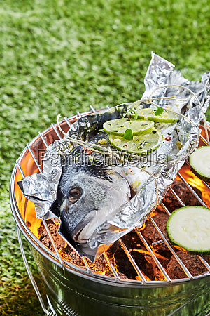 whole fresh raw fish grilling on
