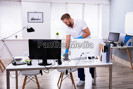 janitor cleaning white desk in office