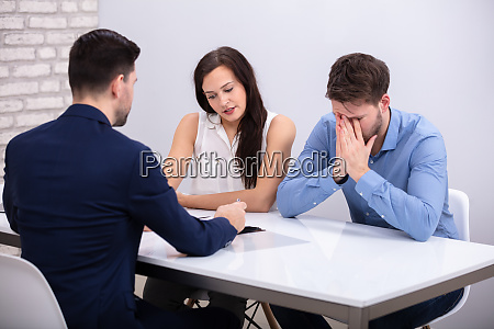 financial advisor sitting with depressed couple
