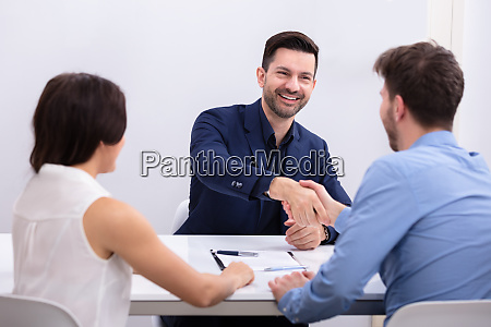 woman looking at businessmen shaking hands