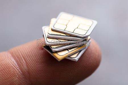 sim cards on humans finger