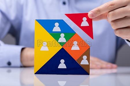 businessman building tangram square block