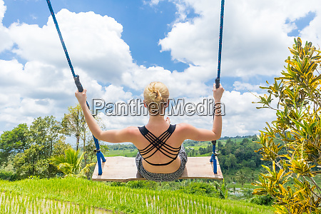 happy female traveller swinging on wooden