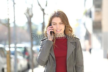 teen walks talking on smart phone