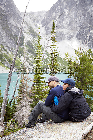 couple admiring mountains and remote lake