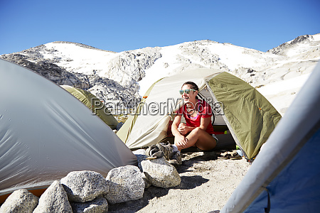 hiker sitting in tent at campsite