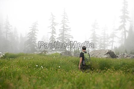 man hiking in rural field