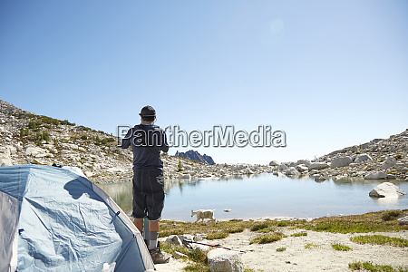man standing at tent at campsite