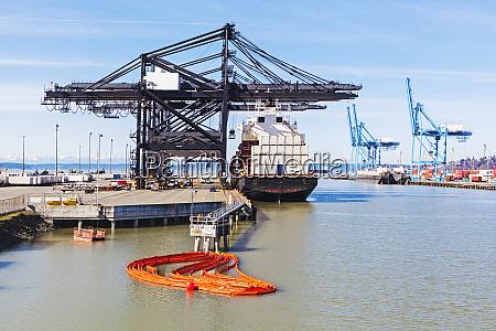 cranes over cargo ship in harbor