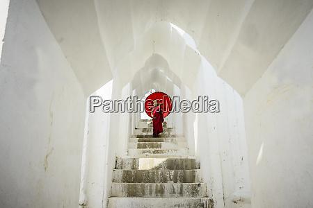 asian monk under umbrella on temple