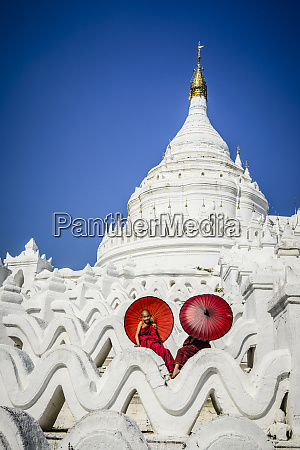 asian monks sitting under umbrellas at
