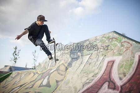 caucasian man skating at skate park