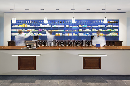 blurred view of pharmacists behind counter