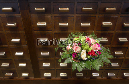 bouquet of flowers near apothecary drawers
