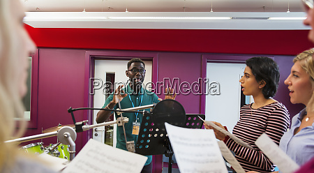 male conductor leading women singing in
