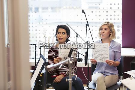 women with sheet music singing in