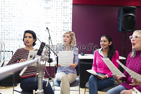 womens choir with sheet music singing
