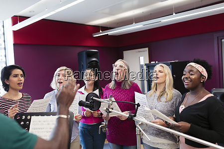 womens choir with sheet music singing