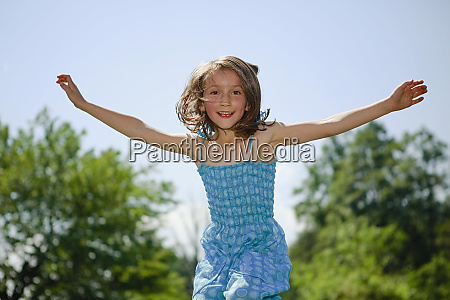 portrait playful girl with arms outstretched
