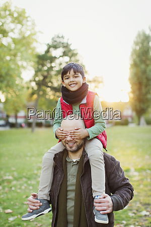 portrait playful son riding on fathers