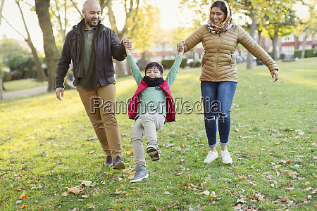 playful muslim family in autumn park