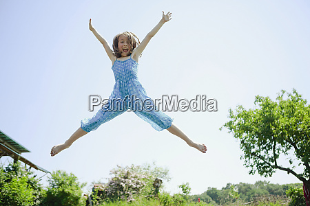 portrait playful carefree girl jumping for