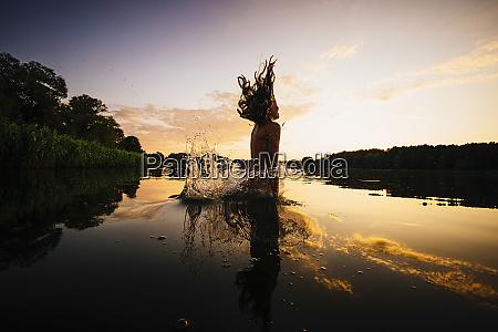 carefree girl jumping into lake at