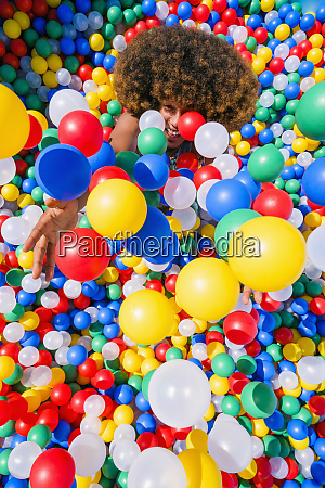 playful young man throwing multicolor balls