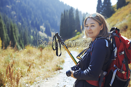 portrait confident young female photographer backpacking