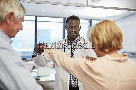male doctor examining senior patients shoulder