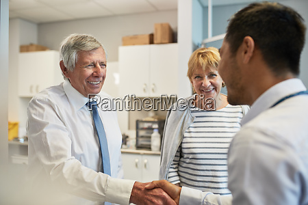 doctor shaking hands with senior couple