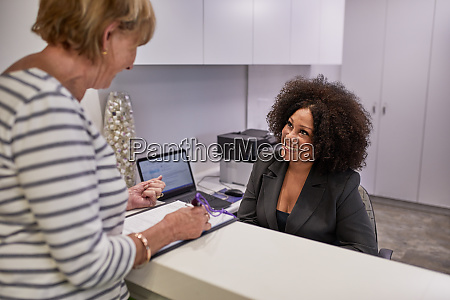 senior woman checking in with receptionist