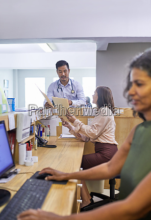 doctor and receptionist with medical records