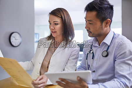 doctors discussing medical record in clinic