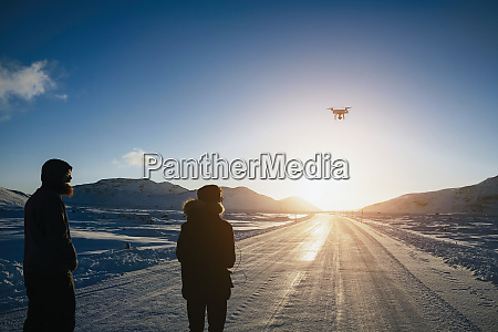 father and son flying drone over