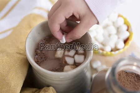 girls hand putting marshmallows in hot
