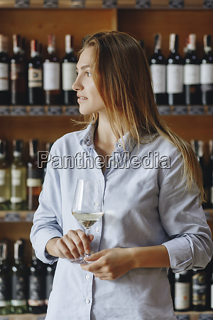 young woman holding glass of white
