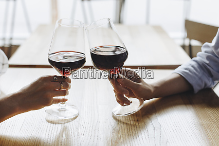 hands of women toasting with glasses
